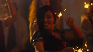 Handheld shot of confident Hispanic woman smiling when performing dance moves with sparklers in hands during party in nightclub