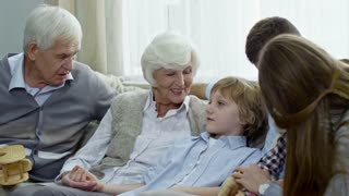 Handheld shot of grandparents and young couple sitting on sofa and talking with little boy while spending time as family