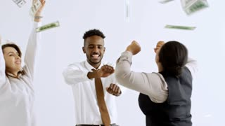Handheld shot of happy group of multi-ethnic businesspeople laughing and dancing isolated on white background as money falling on them from above