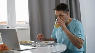 Handheld shot of middle-aged man putting on glasses and using laptop computer when working online from home and eating scrambled eggs for breakfast