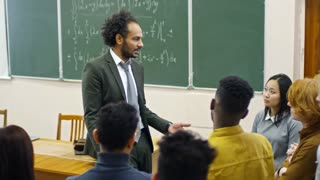 Handheld shot of middle-aged teacher of mathematics talking to multi ethnic group of students standing around him and answering their questions after lecture on calculus