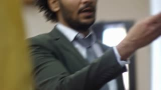 Handheld shot of middle aged university professor pointing at blackboard when asking question to student during lecture