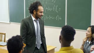 Handheld shot of middle eastern university professor with curly hair talking to multi ethnic group of students, who are asking questions about equations after lecture