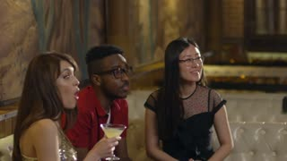 Handheld shot of multi ethnic young people getting together in bar or cafe, smiling and clinking glasses with colored cocktail in them when celebrating something