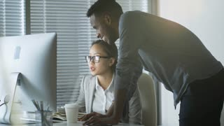 Handheld shot of two young employees of different ethnicities sharing ideas on project, Asian woman sitting at desk and black man helping her with work