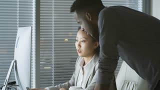 Handheld shot of young Asian woman sitting at desk in office, her black male colleague helping her with work on desktop computer