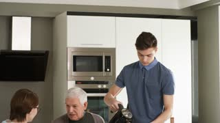 Handheld shot of young man pouring tea or coffee into cups while volunteering with friend and helping senior man at home