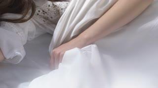 Handheld slowmo shot of sleepy beautiful woman wearing nightgown relaxing in bed in morning
