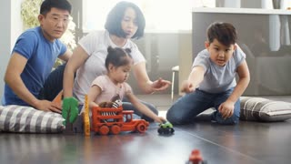 Handheld tracking shot of Asian family of four having fun together: they are sitting on living room floor and playing with toys