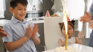Handheld tracking shot of happy Asian schoolboy, cute little girl in party hat and unrecognizable parents clapping and looking at firework candle on birthday cake