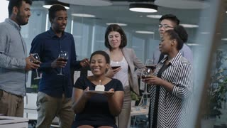 Happy African woman sitting on chair, smiling and blowing out candle on b-day cake while her colleagues standing around with wine glasses and singing a song