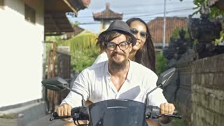 Happy Asian couple riding together on scooter in Bali town and enjoying warm summer day; woman touching green leaves on fence
