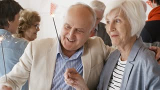 Happy elderly couple embracing and laughing while dancing with sparklers at party