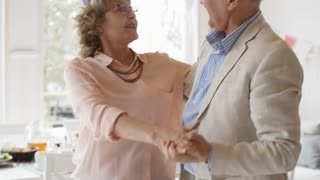 Happy elderly couple in party hats enjoying dancing at the celebration with friends