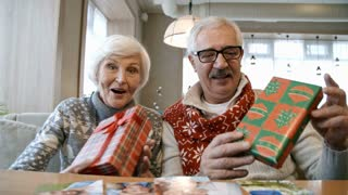 Happy elderly couple sitting on couch at restaurant table, smiling, waving and posing at camera with Christmas gifts