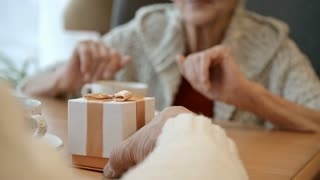 Happy elderly woman taking a gift from husband, opening box and getting excited while having coffee in restaurant