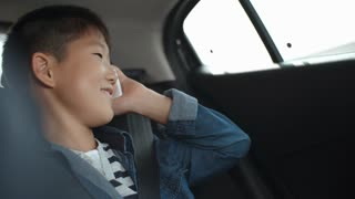 Happy little Asian boy riding on backseat of car, smiling and chatting on mobile phone