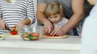 Happy mother, father and little daughter cutting vegetables together on kitchen table while cooking salad at home; parents smiling and talking with son