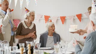 Happy senior woman in birthday hat sitting at celebration table in living room and clapping hands while friends bringing birthday cake with candles and congratulating her; men blowing party horns