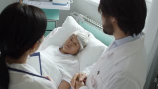 High angle shot of caring male and female doctors in lab coats talking with elderly female patient lying in bed and encouraging her about prognosis, then leaving