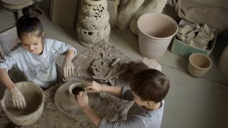 High angle shot of cute elementary school-age girl and boy wetting their hands and throwing pot on spinning pottery wheel in workshop