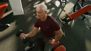 High angle shot of fit elderly man with grey hair training his arms with dumbbell biceps curl exercise in gym