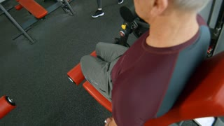 High angle shot of senior man training on leg curl machine and elderly woman walking and warming up arms while doing workout in gym