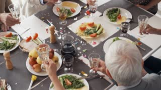 High angle view of elderly friends in party hats having holiday dinner and toasting with champagne