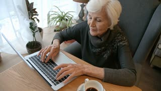 High angle view of elderly woman sitting at cafe table with coffee cup and typing something on laptop