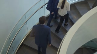 High angle view of employees walking up and down the stairs in business center