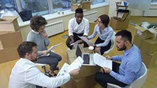 High angle view of multiethnic business team sitting around stack of boxes after moving in new office, discussing documents and then standing up, tossing papers and applauding