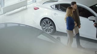 High angle with PAN of Asian saleswoman with clipboard talking with couple choosing car at dealership