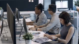 High angled panning shot of diverse team of employees working on computers at desks and discussing something in modern open space office