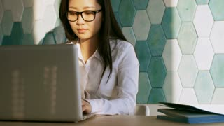 Intelligent young Asian businesswoman in eyeglasses typing on laptop at desk in the office