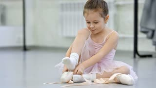 Joyful little girl sitting on the floor in dance studio, trying on pointe shoes and dreaming of becoming professional ballerina