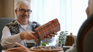 Joyful senior man in eyeglasses taking gift box and greeting card, enjoying it and smiling at holiday dinner in restaurant