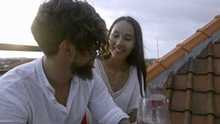Joyous Asian couple sitting on rooftop terrace at sunset, having red wine, smiling and talking while having romantic date