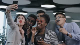 Joyous multi-ethnic team of business men and women holding funny mustache and eyeglasses on sticks, smiling and posing at camera of smartphone while taking selfie at corporate party