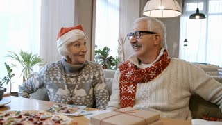 Joyous senior man and woman sitting on couch at restaurant table and sharing Christmas gifts at holiday dinner