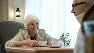 Joyous senior woman sitting at table in coffee shop, smiling and listening to elderly man telling a story