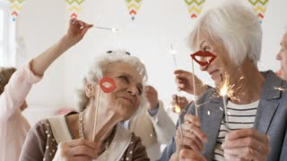 Joyous senior women laughing and dancing with lips on sticks and sparklers while having fun at party with friends