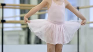Legs of little girl in pink tutu skirt standing on the floor in dance studio and performing clumsy movements in big pointe shoes, tilt down shot