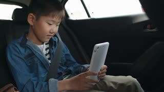 Little Asian boy riding on backseat of car and playing on modern digital tablet