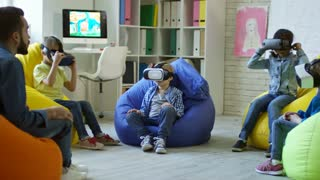 Little boys and girls sitting on colorful bean bag chairs and watching educational video in VR glasses while male teacher talking to them