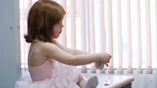 Little girl in pink tutu skirt and leotard sitting in dressing room in dance studio and putting on ballet shoes