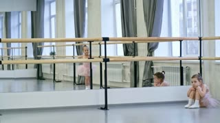 Little girl sitting sad and tired on the floor and looking at other girls who are jumping around in dance class
