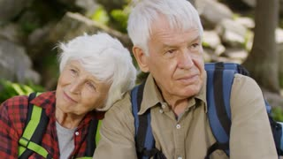 Loving senior couple sitting with backpacks in forest, smiling and enjoying nature around while taking a break during hiking on summer vacation