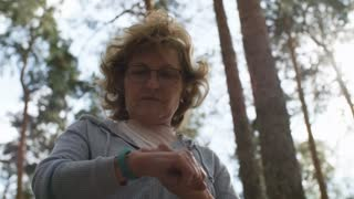 Low angle dolly shot of elderly woman in glasses walking in forest in morning and touching screen of fitness wristwatch, then starting jogging