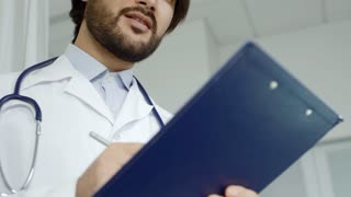 Low angle of male Asian doctor in lab coat smiling and writing notes on clipboard while listening to patient off camera