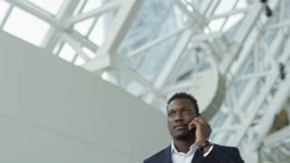 Low angle of successful African businessman in suit smiling and talking on phone